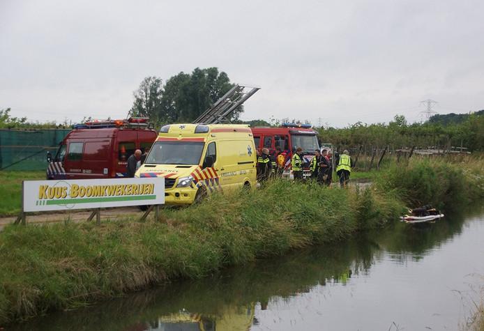 De rode tractor viel door nog onbekende oorzaak in het water. De bestuurder kwam klem te zitten.