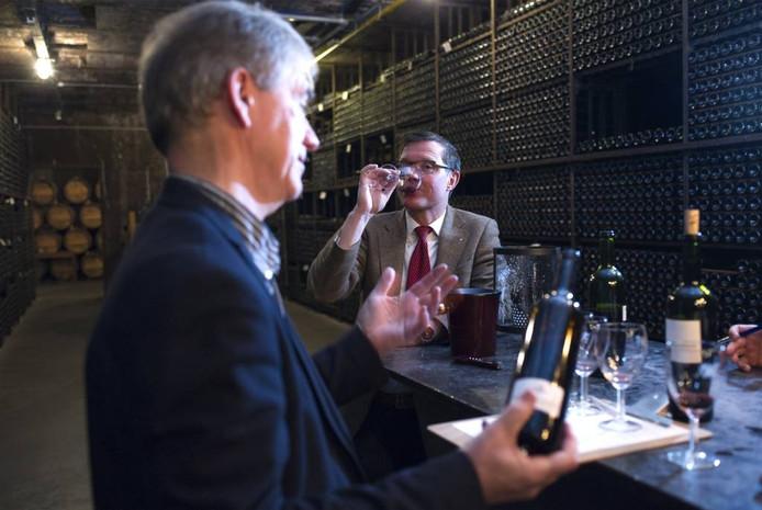 Chris Alblas (voorgrond) en Marcel Donders proeven in de kelder van Robbers & van den Hoogen de jubileumwijnen.