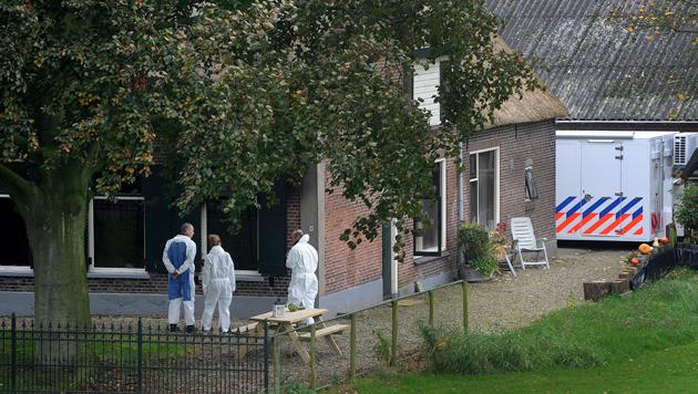Rechercheurs onderzoeken het terrein rond de boerderij waar na een brand de lichamen van vier gezinsleden zijn gevonden