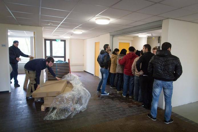 Asielzoekers checken in aan de balie van het nieuwe asielzoekerscentrum, terwijl links nog kinderbedjes worden aangevoerd.