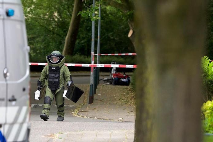 Een medewerker van de EOD loopt weg van de tas waarin mogelijk explosieven zitten, die op de achtergrond is te zien.