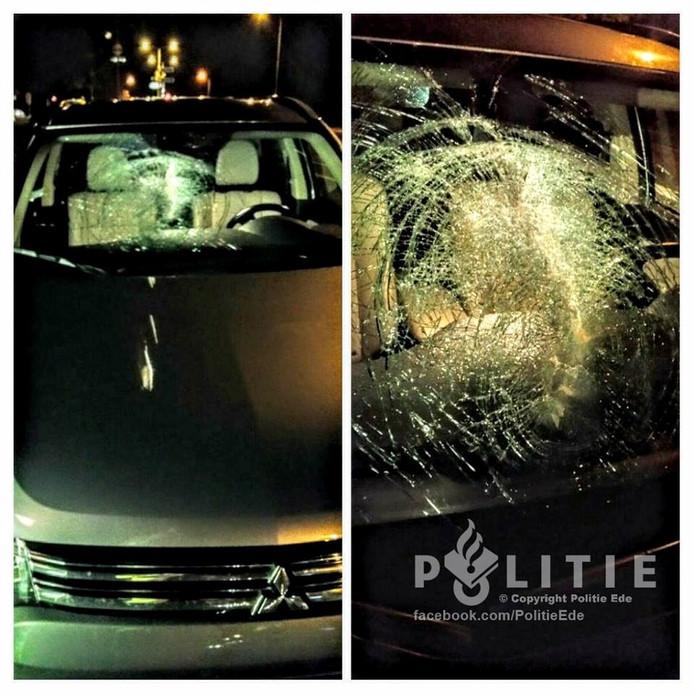 Een klinker raakte de voorruit van de auto die achter de blauwe bestelbus reed.