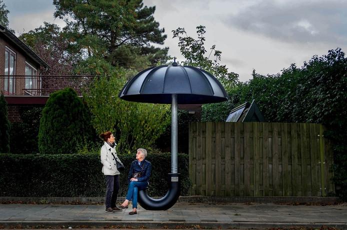 Droog en hip wachten op de bus in Wijchen: onder een mega-paraplu.