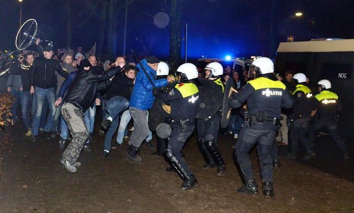 De ME en relschoppers in gevecht voor het gemeentehuis in Geldermalsen. Achteraan maakt iemand zich klaar een fiets te gooien.