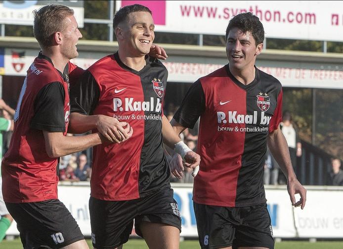 Rick Verbeek (links) en Twan Smits (rechts) feliciteren ploeggenoot Robert Mutzers van De Treffers met zijn eerste goal tegen HSC'21.