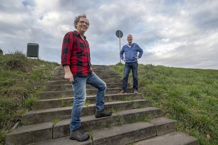 """Martin Knippers (links) en Johan Uittenhout op de dijk in Heteren. """"De Heterun voorziet in een behoefte. Het dorp was aan een gezamenlijk groot evenement toe."""" Marina Popova."""