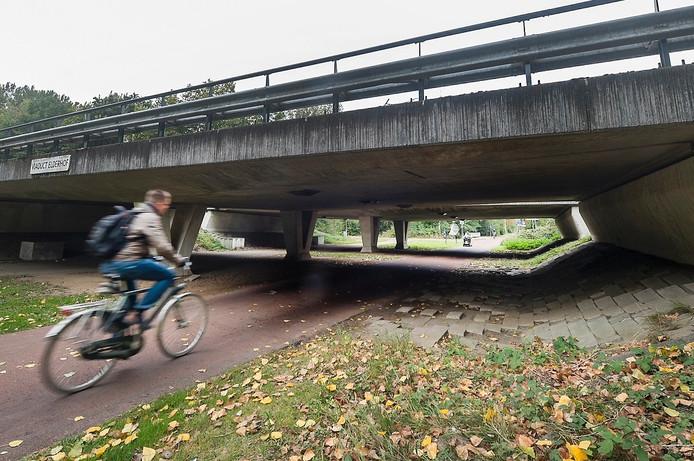 Een man fietst onder de fietstunnel door bij azc Elderhoeve.