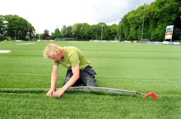 Een medewerker van Ceelen bezig met nieuw kunstgras op Sportpark De Eendracht, in 2009.