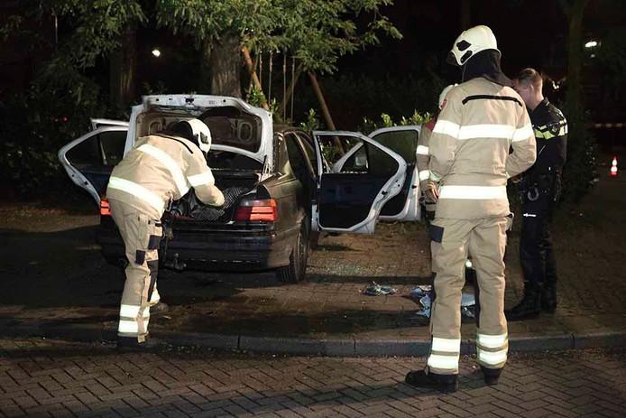 Brandweerlieden controleren de auto die in brand stond.