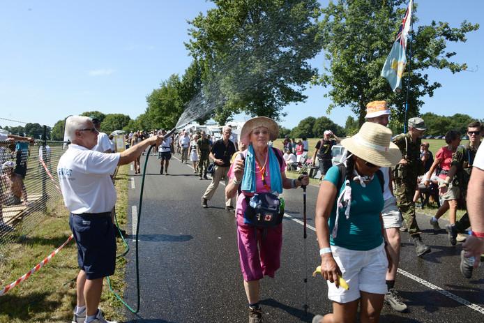 Een omstander verkoelt het wandellegioen met een tuinslang tijdens de Vierdaagse 2013.