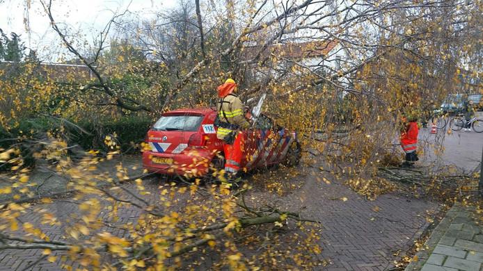 De boom kwam op de motorkap van de brandweerauto terecht.