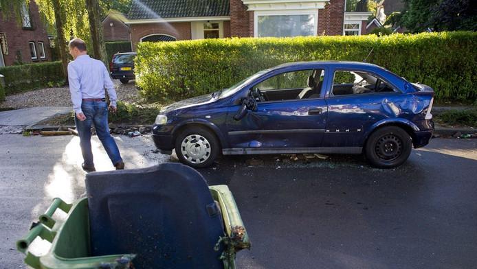 Een gesloopte auto en een vuilcontainer staan op de Stationsweg in Haren.