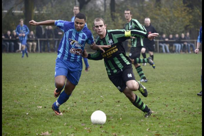 Ronny Schröder (L) van Milsbeek in duel met Hapse Boys-aanvoerder Thijs Kemperman.
