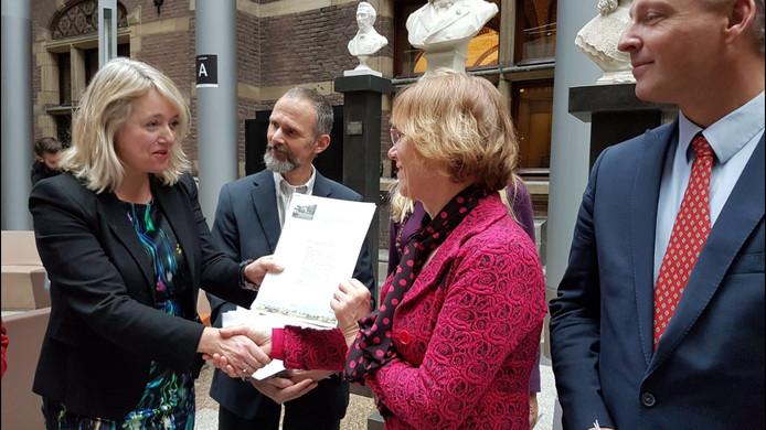 Annette van den Bosch, biedt namens honderden bewoners, de petitie aan aan de voorzitter van de vaste kamercommissie.