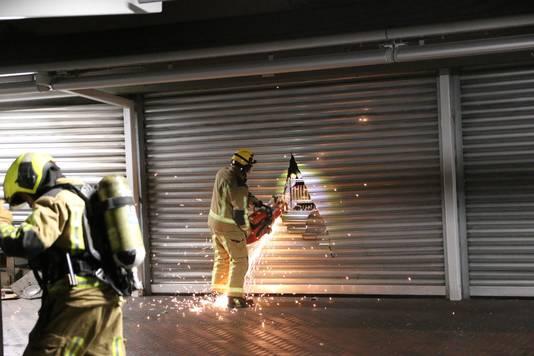 De brandweer moest de deuren open zagen om bij de brand te komen