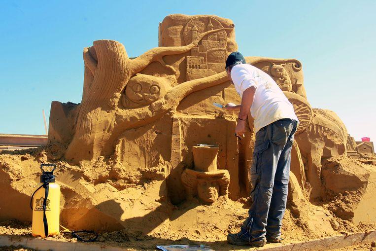 Een artiest werkt aan een zandsculptuur uit Alice in Wonderland.