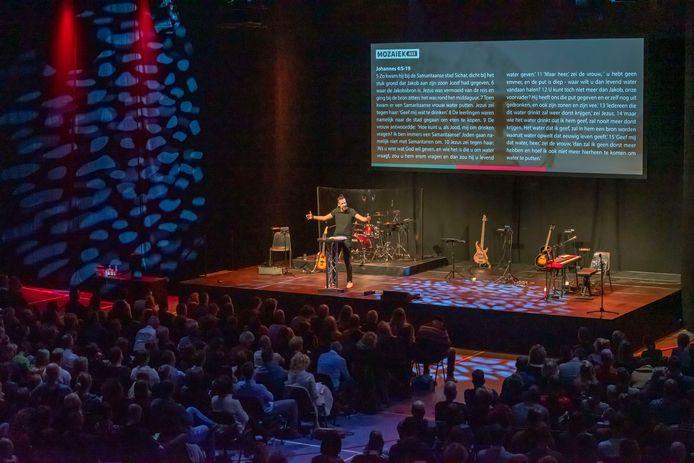Voorganger Arjen ten Brinke spreekt de 1200 aanwezigen toe in sporthal Corlaer in Nijkerk, waar de snel groeiende gemeente Mozaiek sinds twee weken kerkt.