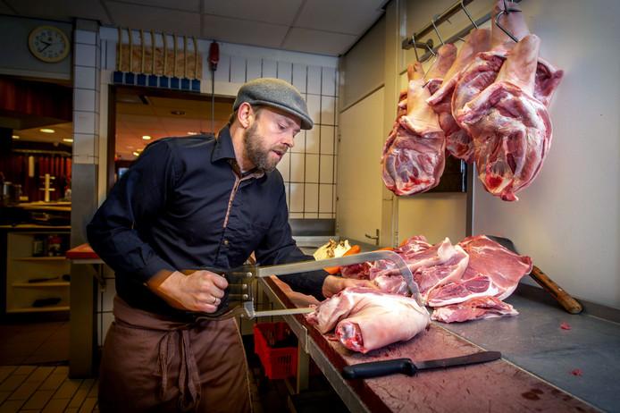 Slager Wilbert Dekkers is druk bezig om het vlees voor de erwtensoep in stukken te snijden.