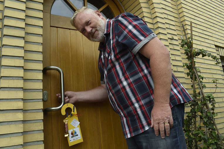 Paul Lermytte, een van de drijvende krachten achter burendag in Deurne, hangt een attentie aan de deur van buurtbewoners.