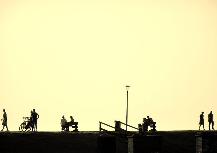 OP AFSTAND Tegenlichtopname waarbij goed de 1,5 metermaatschappij te zien is. Genieten van de ondergaande zon, ruimte genoeg voor iedereen op de Zeedijk van Westkapelle.