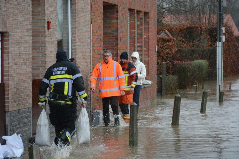 Burgemeester Jos Stassen helpt zandzakjes dragen in de Barbierstraat.