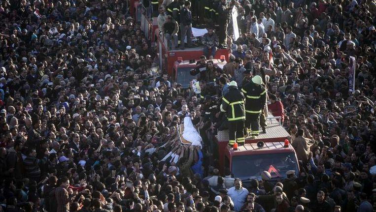 Egyptenaren dragen het lichaam van een van de omgekomen politieagenten van de bomaanslag van afgelopen dinsdag. Beeld afp