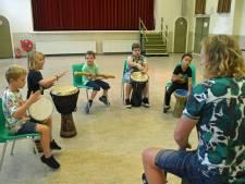 Trommelend terug in de tijd: kinderen roeien op het ritme van de slagen