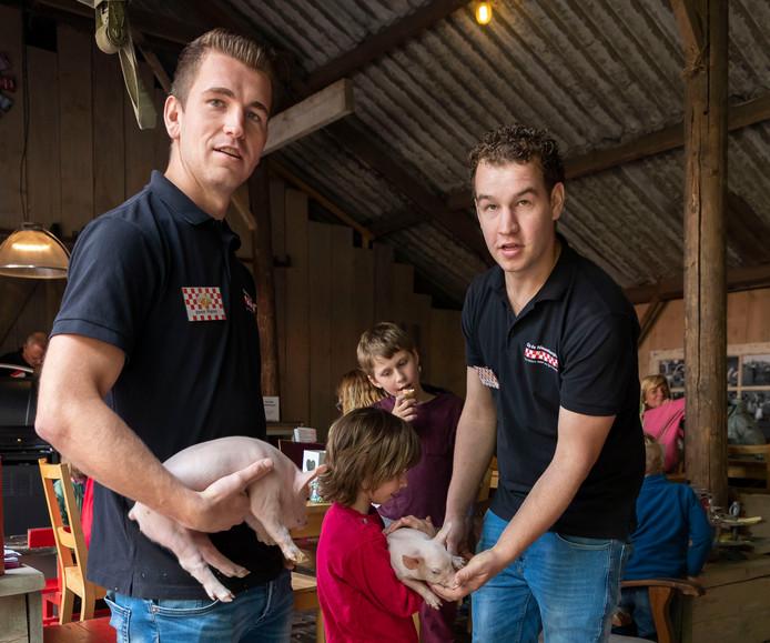 De broers Rens (links) en Guus Leeijen laten kinderen knuffelen met de biggetjes.