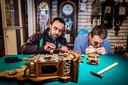 Mustafa Saeed en Jan-Bert van Laren buigen zich over een uurwerk in de klokkenwinkel van Van Laren in de Voorburgse Herenstraat. De Sallandse klok op de voorgrond is door Saeed gerepareerd. ,,Niet eerder zo'n Hollandse klok in handen gehad.''