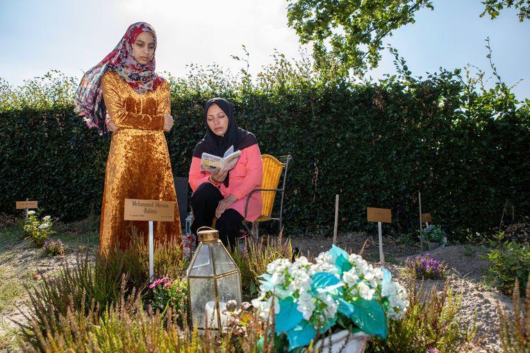 Zus Sogand Rahimi en moeder Delmira Husseini bij het graf van Meesam. Beeld Negin Zendegani