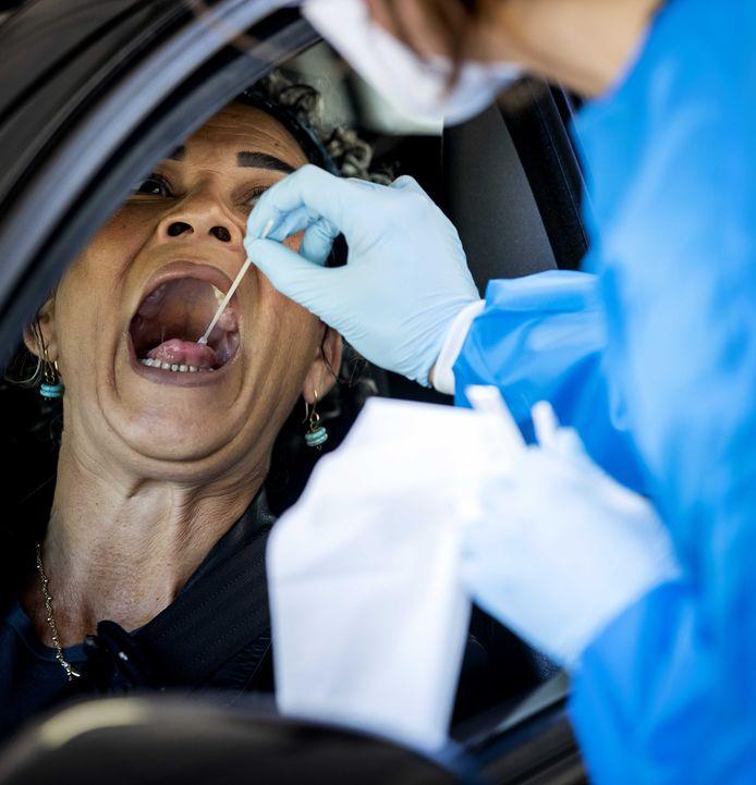 Een medewerker van de GGD Gooi en Vechtstreek neemt een coronatest af in een testlocatie.