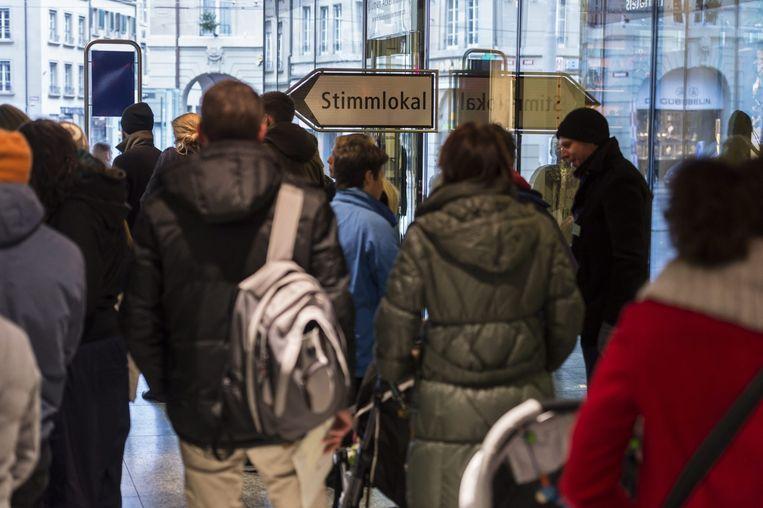 Zwitsers wachten op hun beurt in een stemlokaal voor een referendum in het Bern, 30 november 2014. Beeld epa