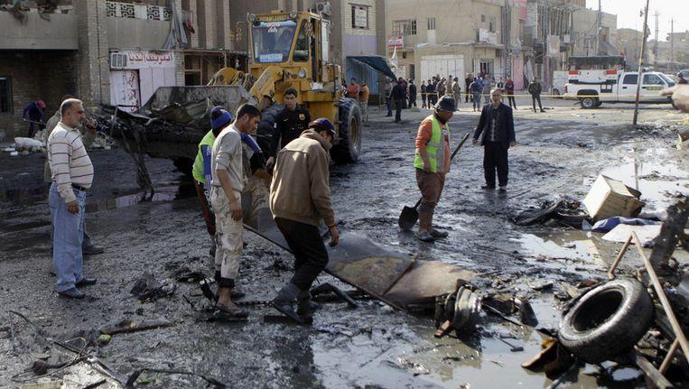 Inwoners van Bagdad ruimen de ravage op die veroorzaakt werd door een autobom, afgelopen januari. Beeld ap