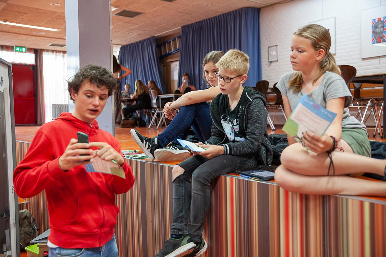 Leerlingen krijgen van andere jongeren van Team Alert instructies over het gevaar van het gebruik van een mobieltje op de fiets.  Beeld Harry Cock