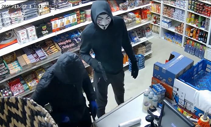 Bewakingsbeeld van de twee overvallers. Links de man met de kobaltblauwe werkhandschoenen, rechts de jongen met het masker dat bekend is uit de film V for Vendetta.