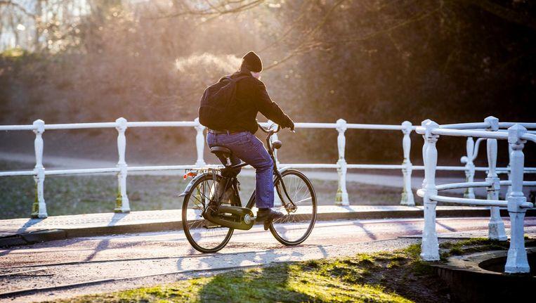 Een man fietst over een brug door de kou. Beeld anp