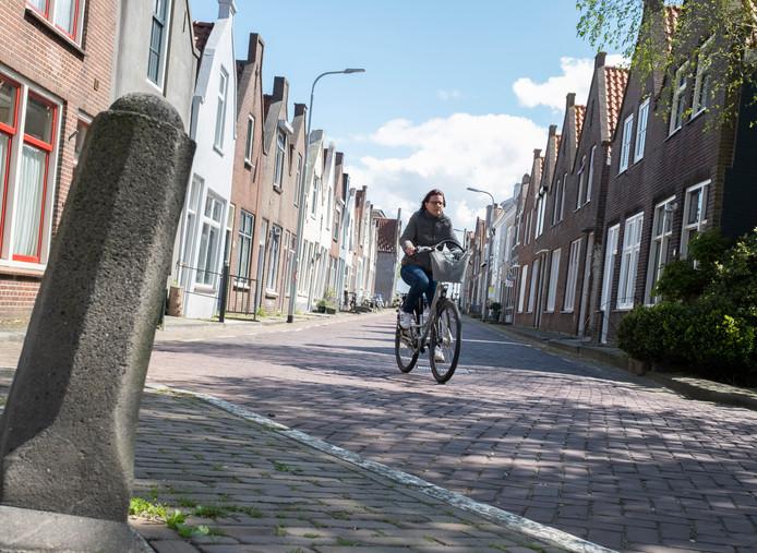 Verleden en heden met monumentenpandjes en huidig verkeer in de Hoofdpoortstraat.
