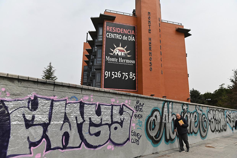 Een man loopt langs Monte Hermoso in Madrid, waar al twintig van de 130 bewoners aan het coronavirus zouden zijn overleden. De Spaanse justitie heeft woensdag een onderzoek naar de gang van zaken in het bejaardentehuis ingesteld. Beeld EPA