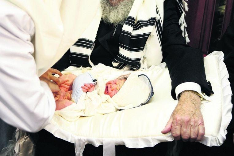 Rabbijnen voeren een besnijdenis uit bij een acht dagen oud jongetje. © Reuters Beeld