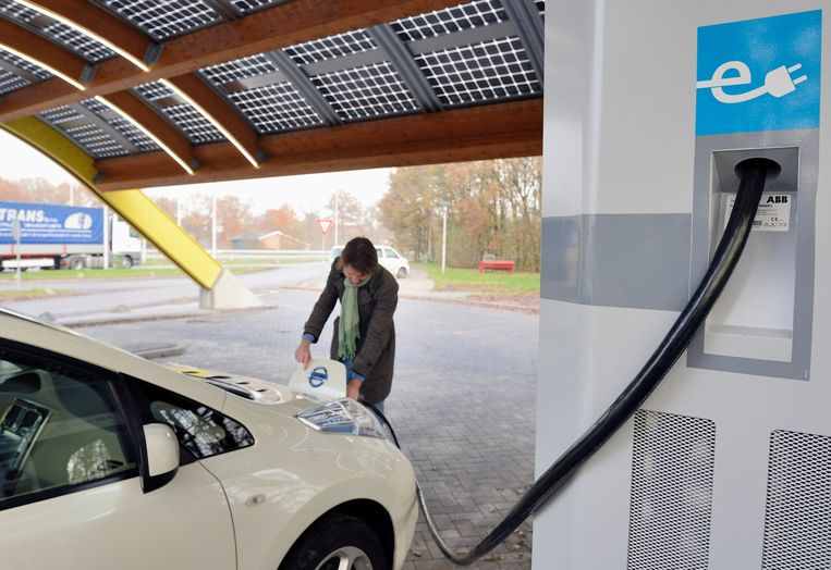 Een automobilist laad zijn elektrische auto. Beeld ANP