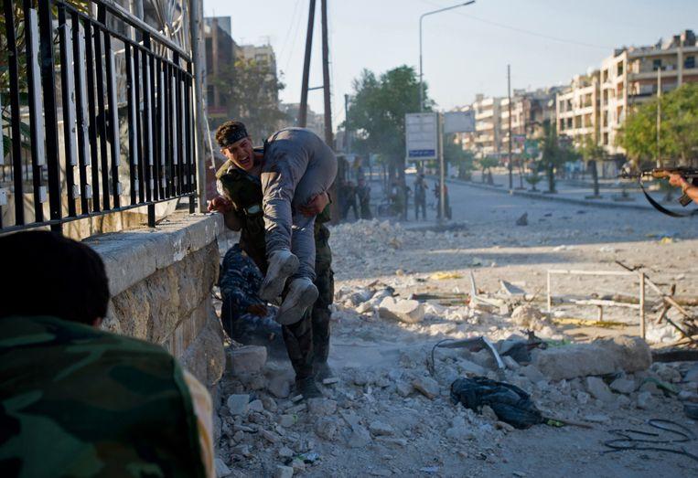 Aleppo 2012, een rebellenstrijder draagt zijn gesneuvelde broer de vuurlinie uit.  Beeld AFP
