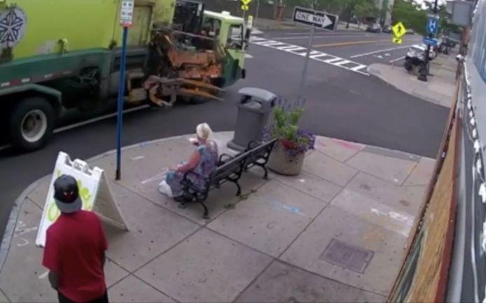 Un camion à ordures emporte une femme assise sur un banc.
