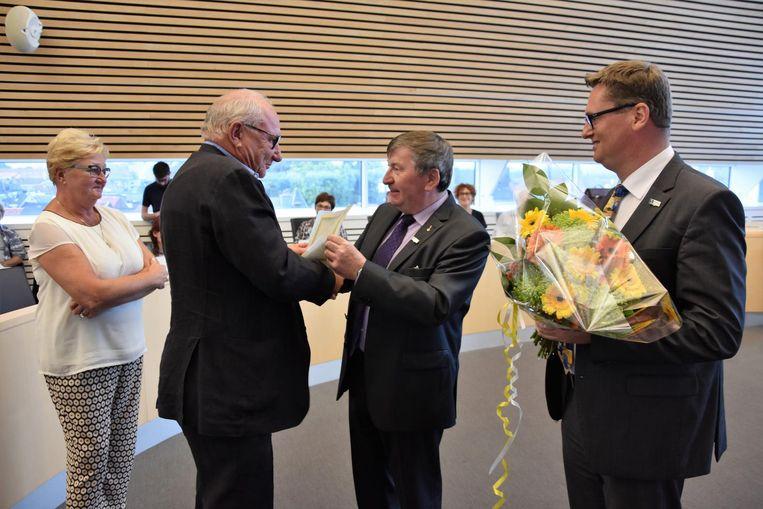 Burgemeester Luc De Ryck en gemeenteraadsvoorzitter Koen De Jonghe zetten Freddy Verbeke en zijn echtgenote in de bloemetjes.