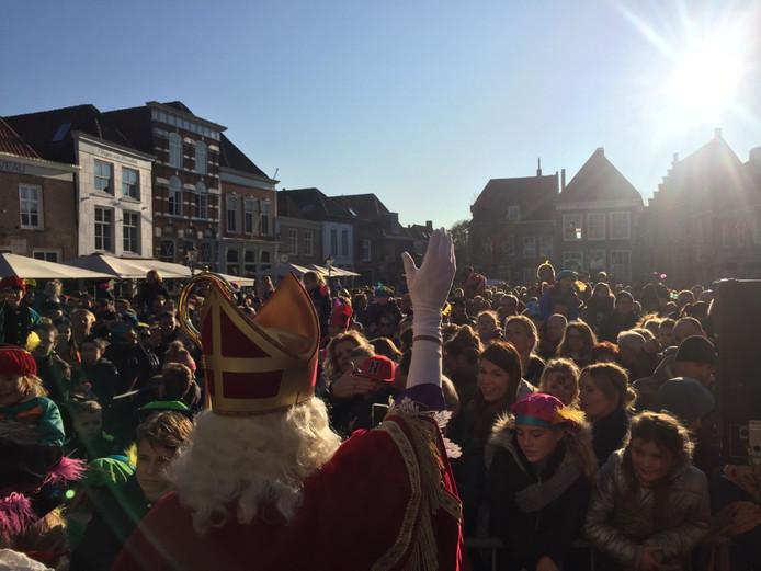 Sinterklaas zwaait de kinderen en hun ouders toe