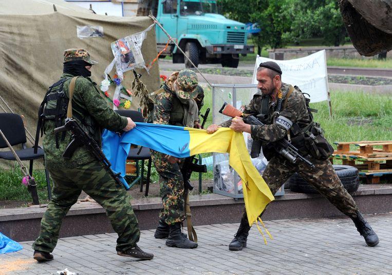 Soldaten van het pro-Russische Vostok-bataljon in Donetsk scheuren een Oekraïense vlag doormidden op 29 mei, 2014. Beeld afp