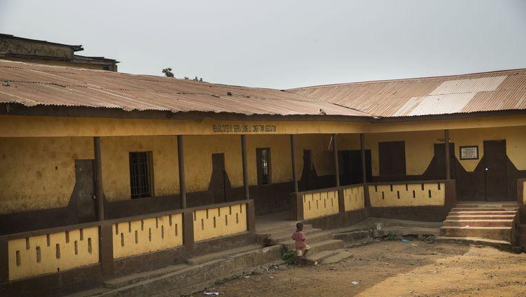 Een jongetje bij een nog gesloten school in Sierra Leone. Beeld null