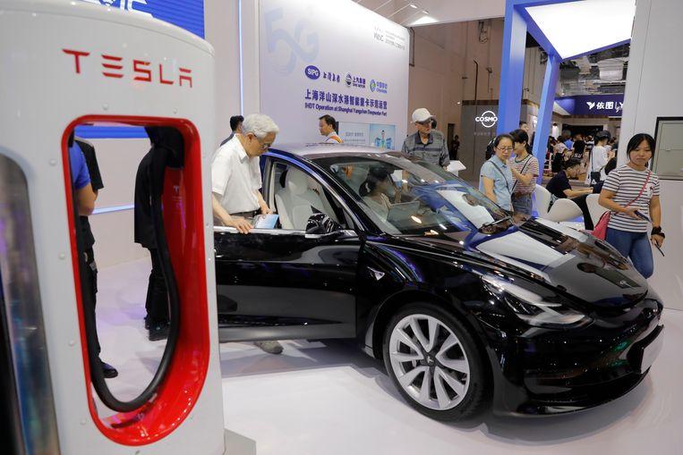 Belangstellenden bekijken een Tesla model 3 op de World Artificial Intelligence Conference (WAIC) in Shanghai. Beeld EPA