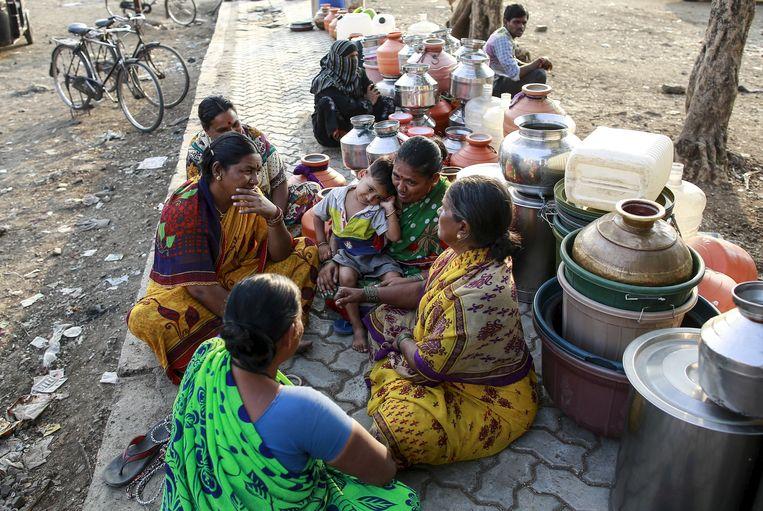 Mensen wachten met kommen aan de drinkwaterophaling in de staat Maharashtra. Beeld REUTERS