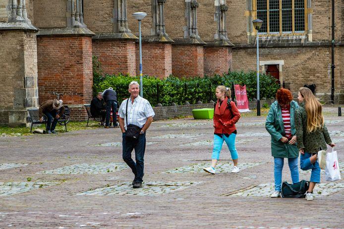 Bezoekers van de binnenstad kuieren over het Grote Kerkhof, met op de achtergrond vaste klanten op de bankjes naast de kerk.