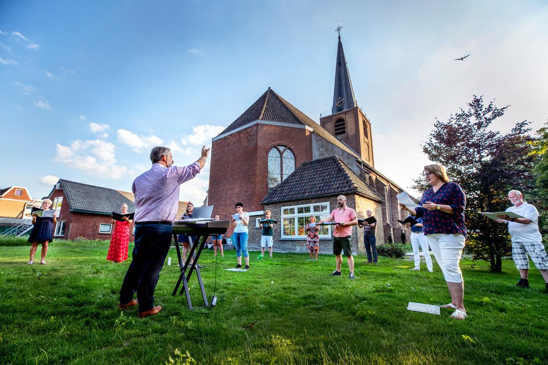 Het koor The New Choral Singers is onder leiding van dirigent Freek Elbers weer begonnen met de repetities. Op gepaste afstand, in de tuin van de kerk in Wateringen. Beeld Raymond Rutting / de Volkskrant